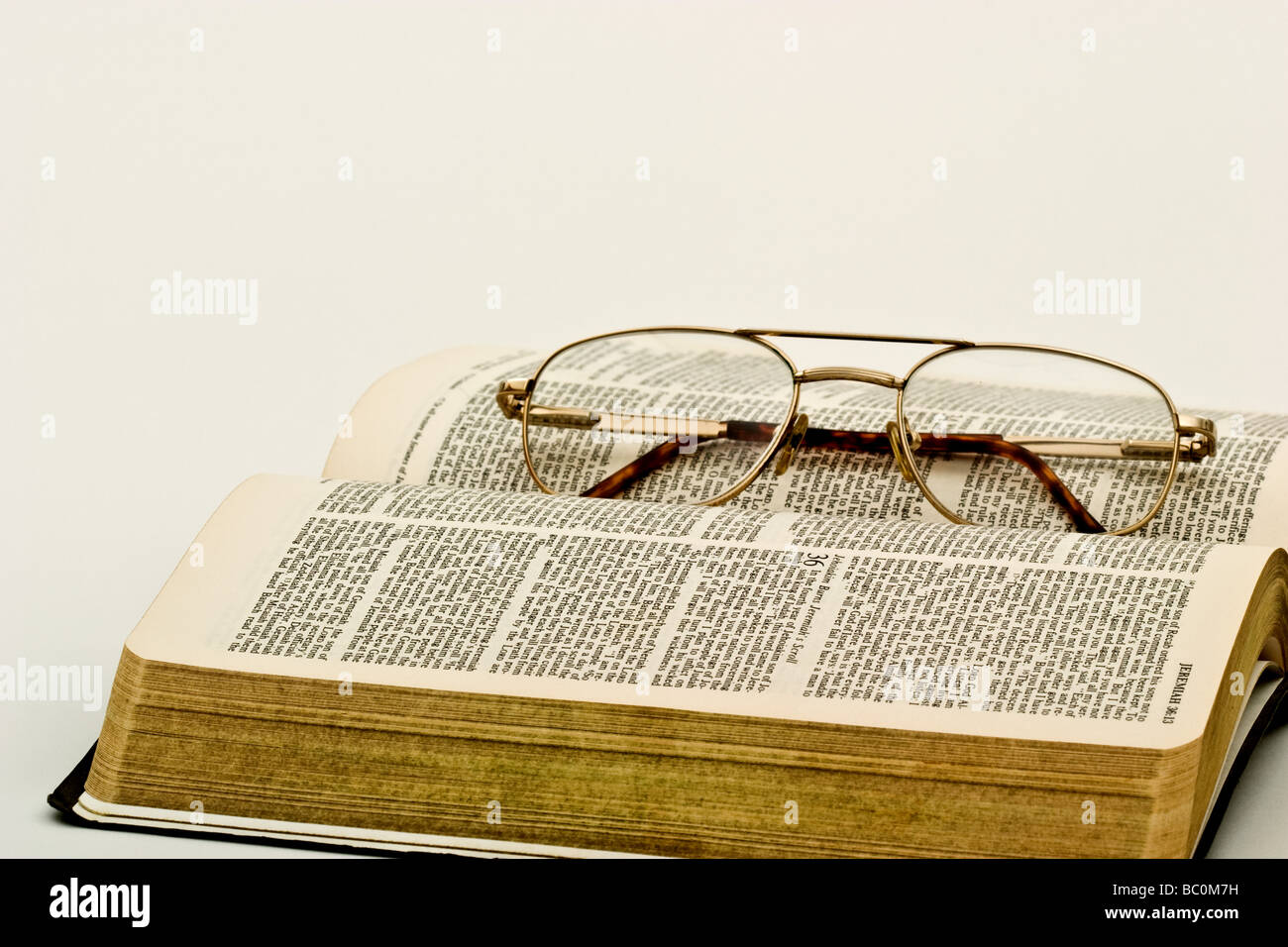 Reading glasses on top of an open book - Stock Image