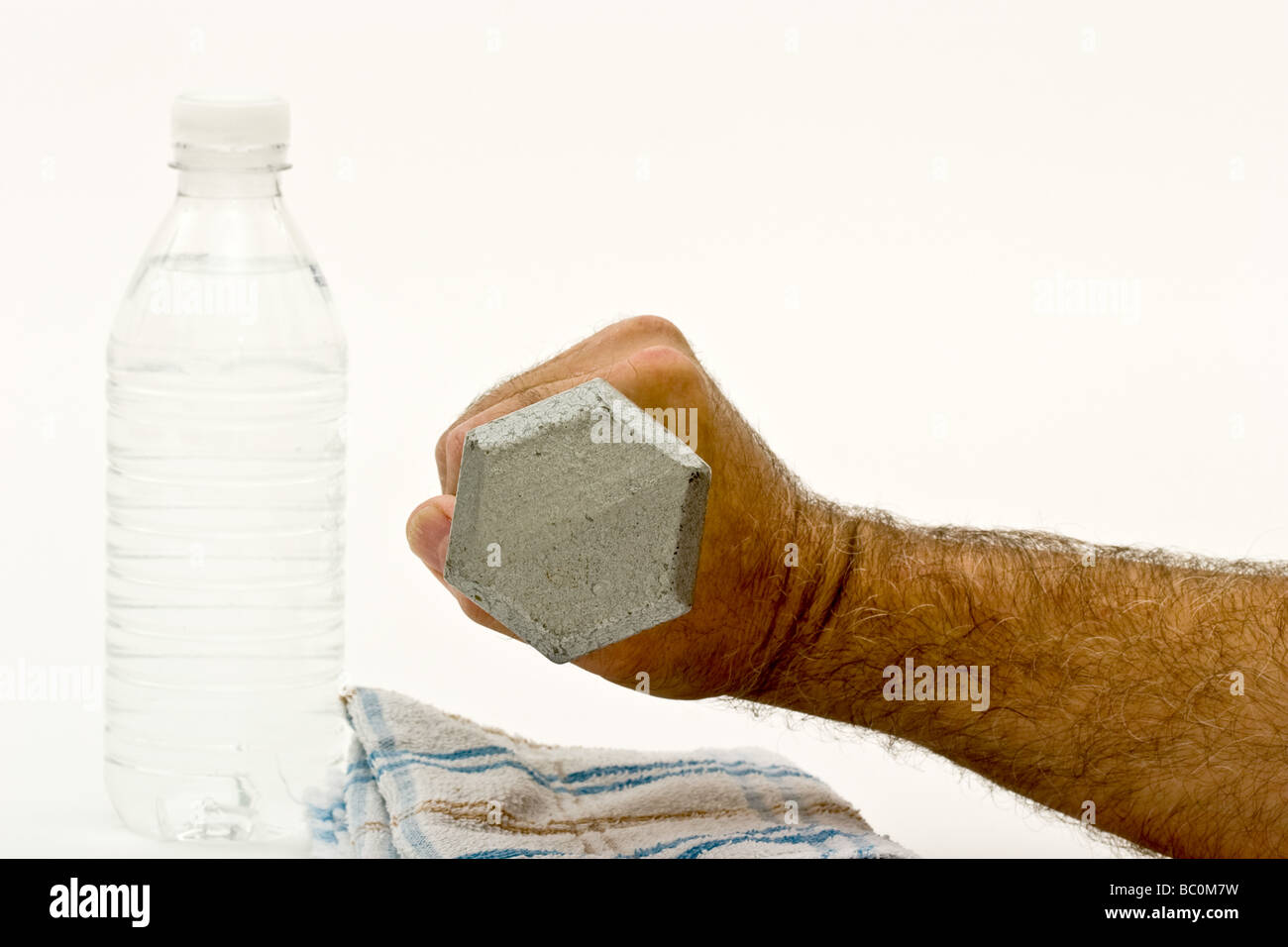 Man's hand holding a dumbbell over a sweat towel next to a bottle of water - Stock Image