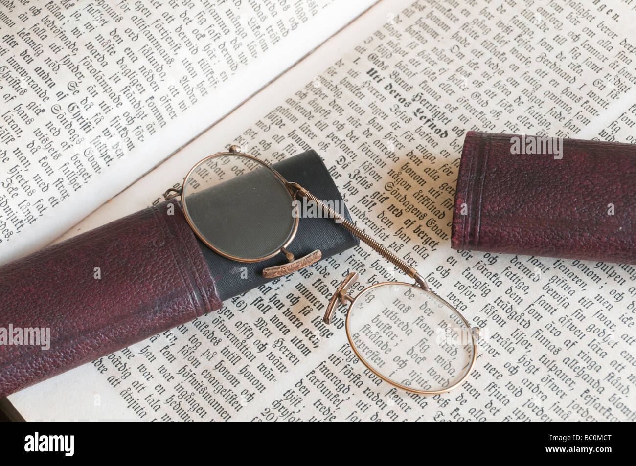 A pair of old pince-nez eye-glasses with case on old Swedish bible. Stock Photo