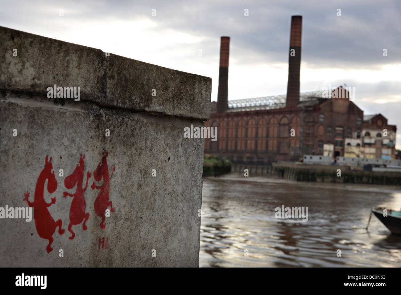 Shot of the River Thames with abandoned factory and three little horses graffity. - Stock Image