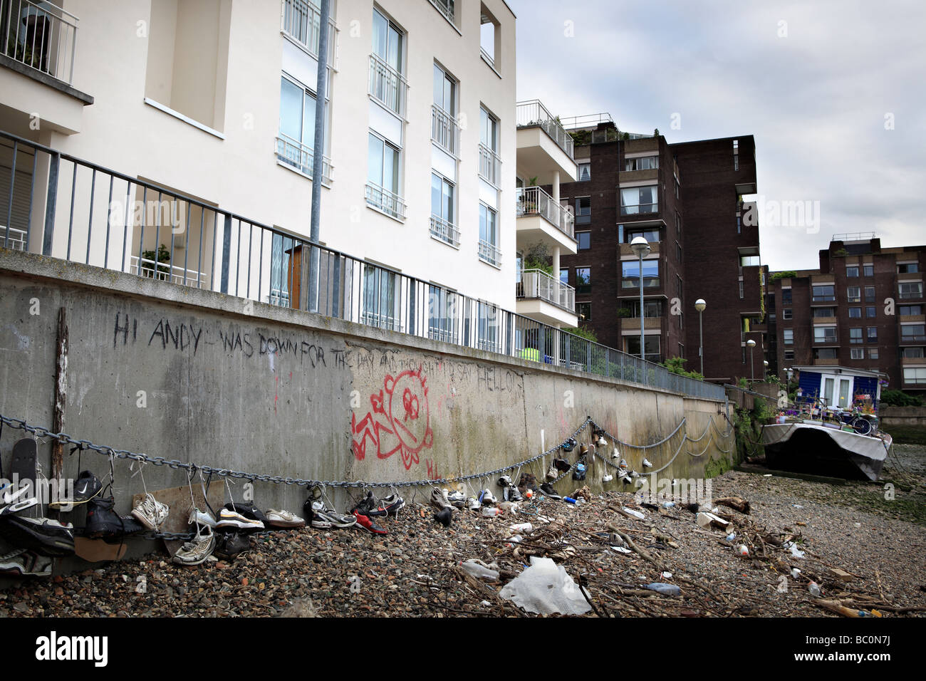 The river Thames' bank full of abandoned shoes and graffitis. - Stock Image
