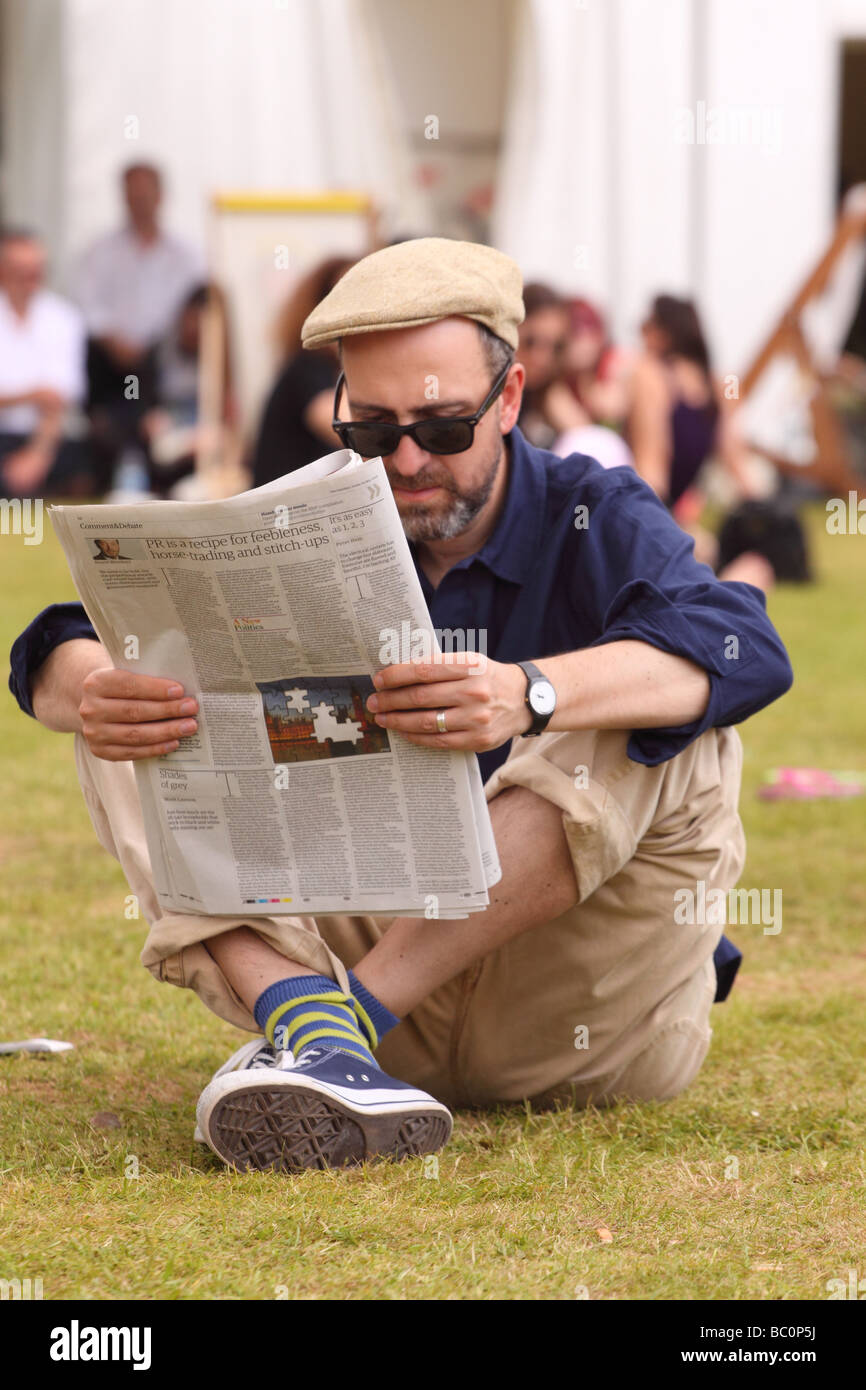 Hay Festival male visitor relaxing reading a newspaper on grass lawn in sunshine at Hay on Wye book festival - Stock Image