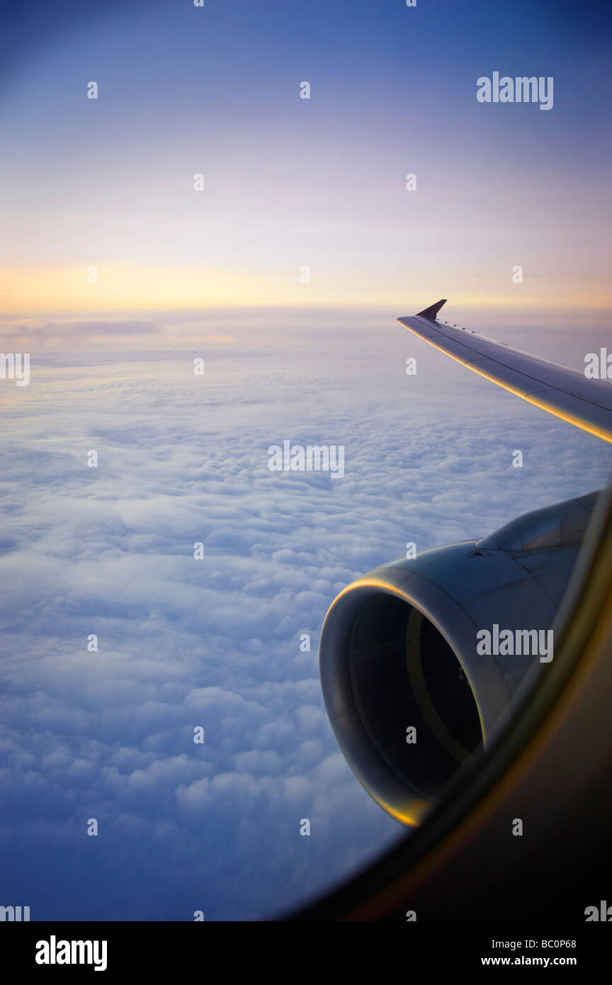 Jet Engine And Wing During Flight At Sunset Stock Photo