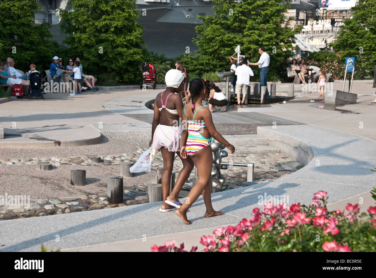 sassy pre-teen black bathing beauties take a stroll around the water park on pier 84 of the Hells Kitchen Manhattan - Stock Image
