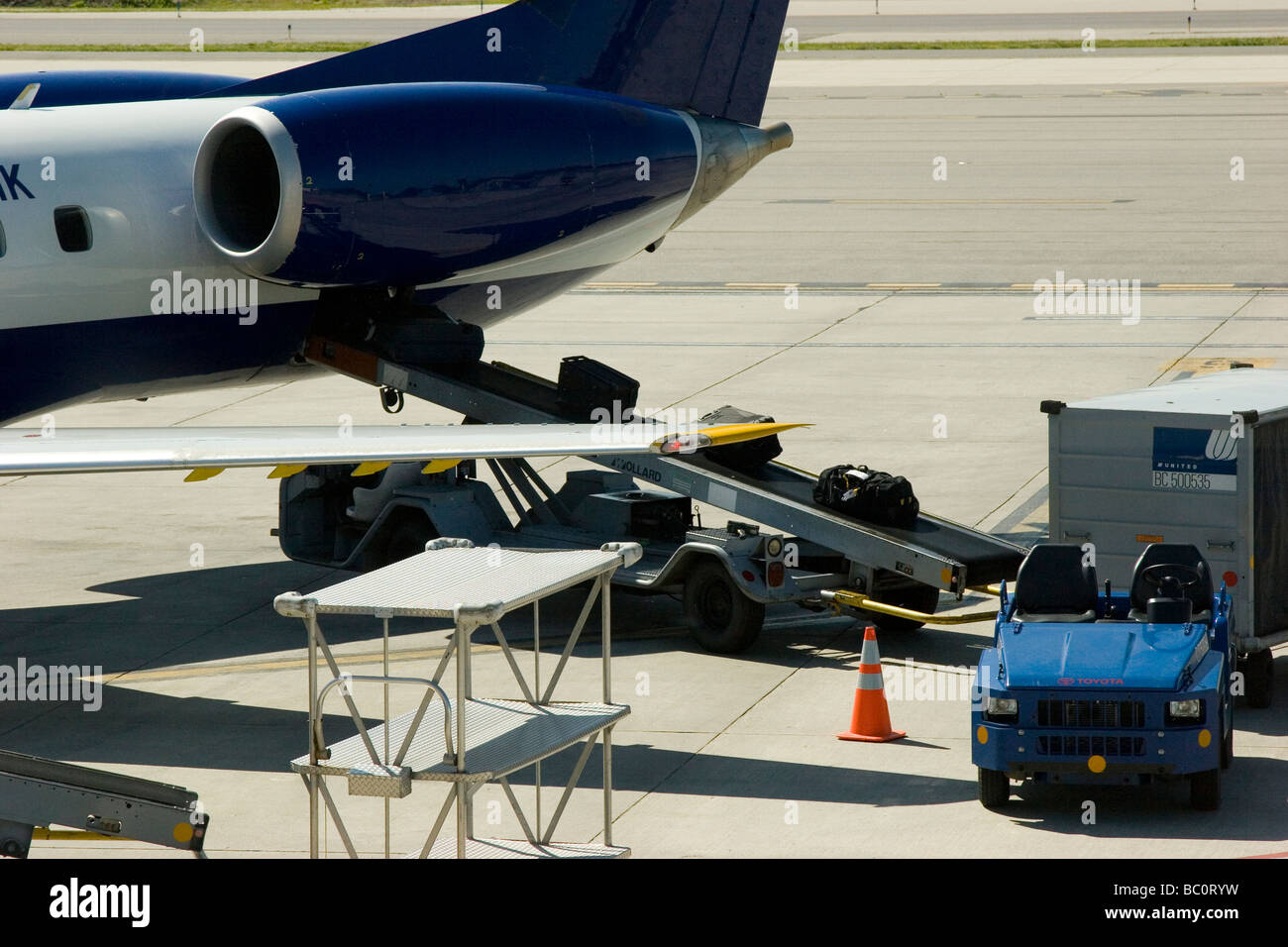 Airplane on tarmac being loaded with luggage - Stock Image