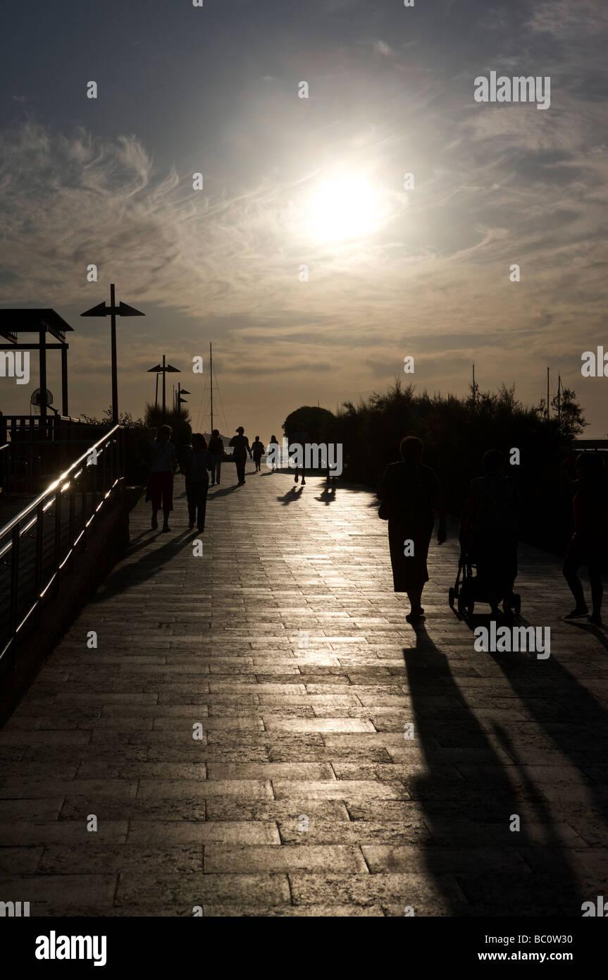 ibiza , san antonio ,spanish familes walking at sunset on promenade - Stock Image