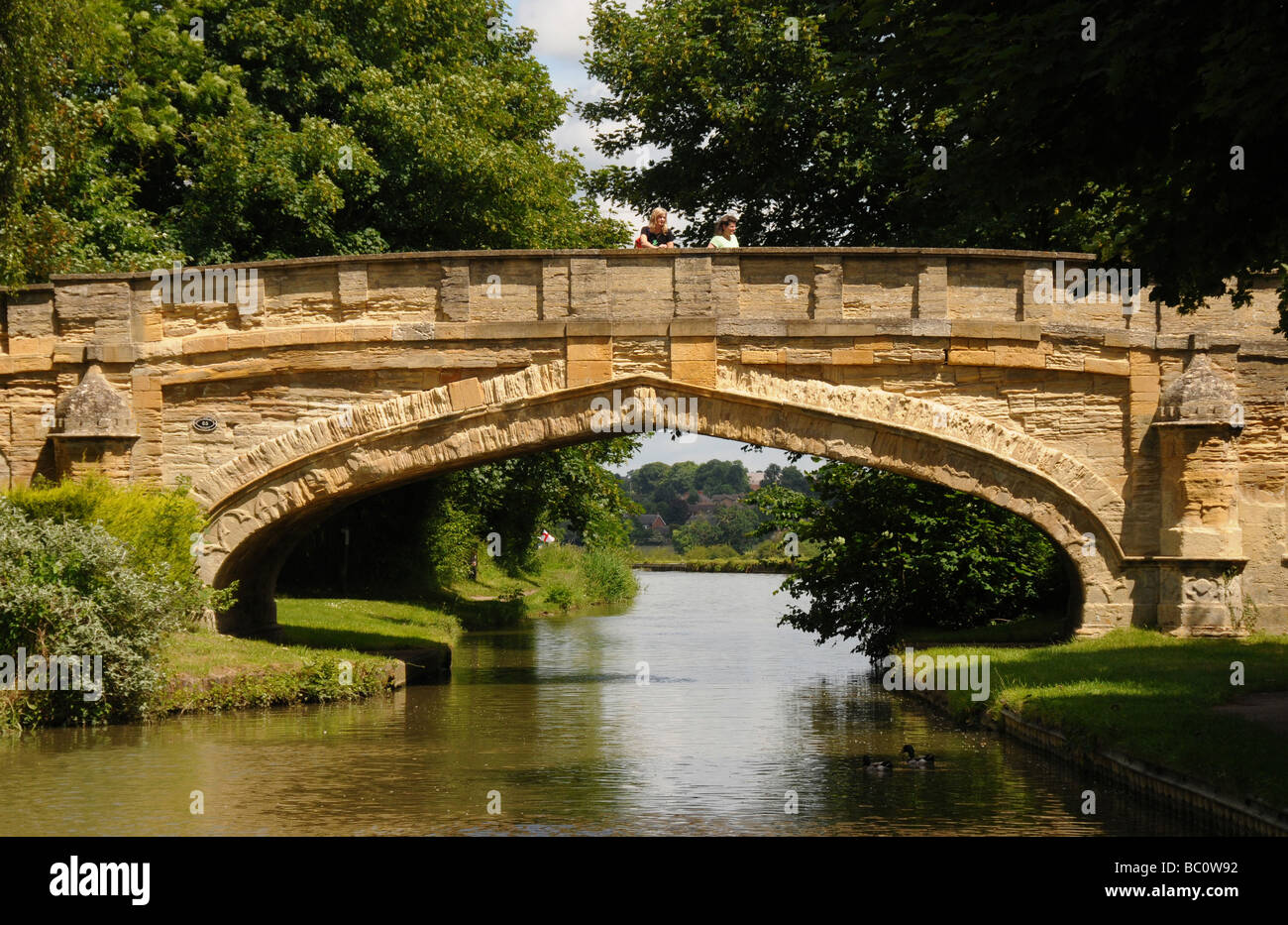 A stone bridge over The Grand Union canal in the village of Cosgrove, Northamptonshire. - Stock Image