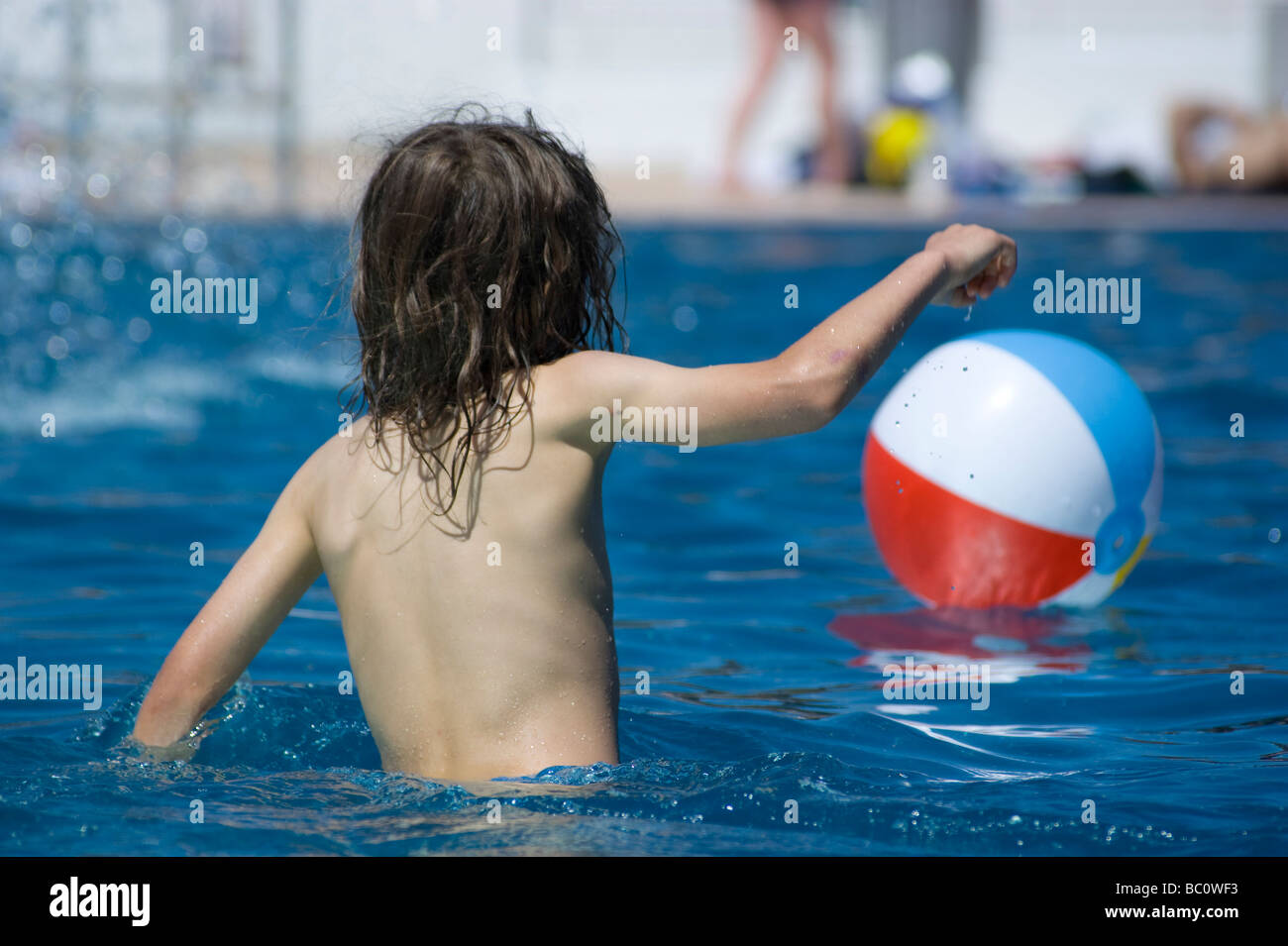 Seven year old boy plays in the refurbished Hampstead Lido with a beach ball on a very hot day in May 2009. - Stock Image