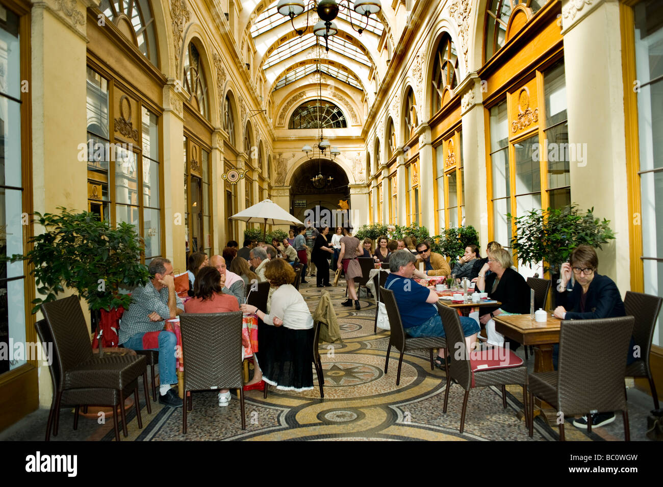 Paris France, French Cafe, Bistro Restaurant, people Sharing Drinks on Crowded Terrace tables in 'Passage Vivienne' - Stock Image