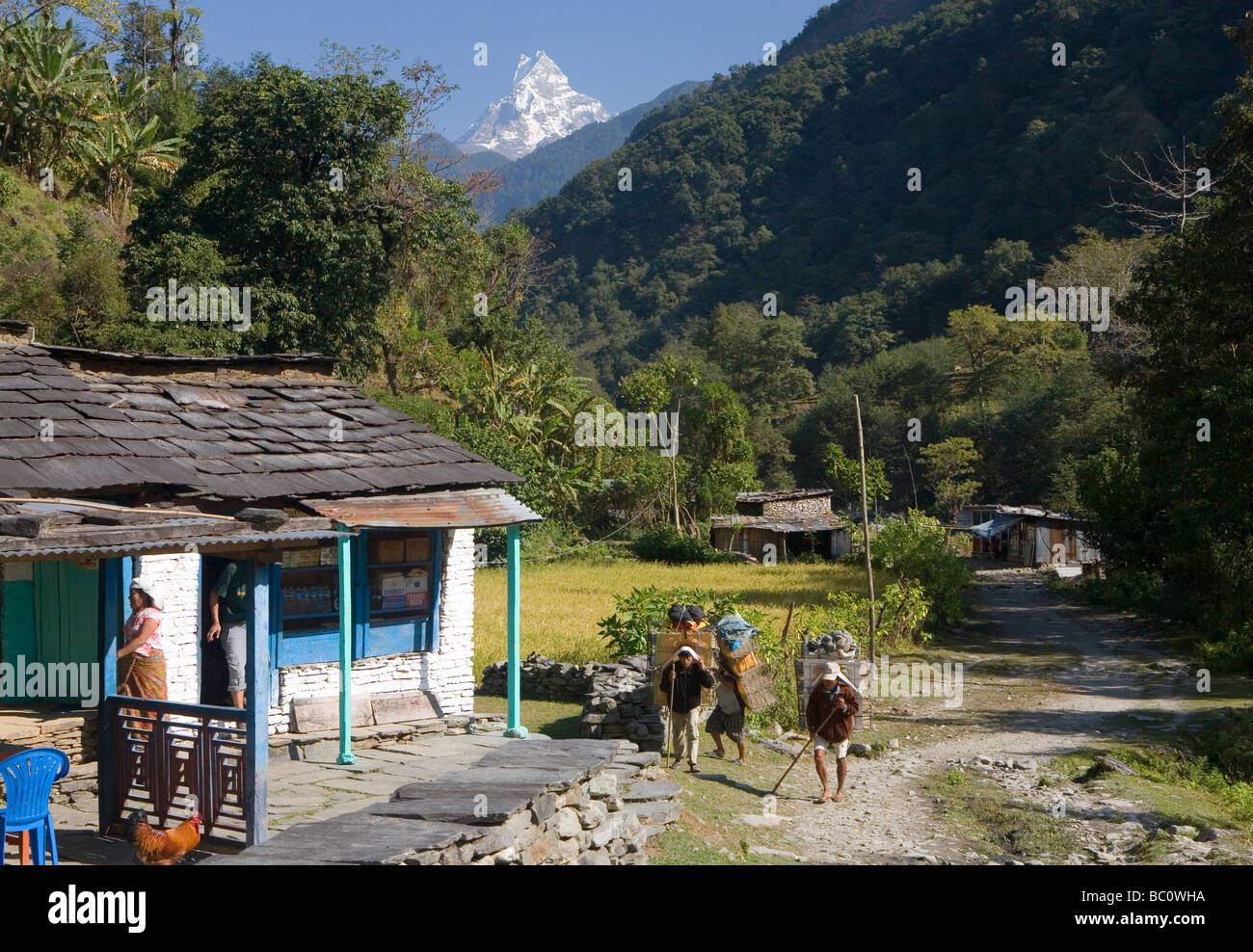 Porters trekking through the village of Shauli Bazaar with Machhapuchhare rising behind - Stock Image