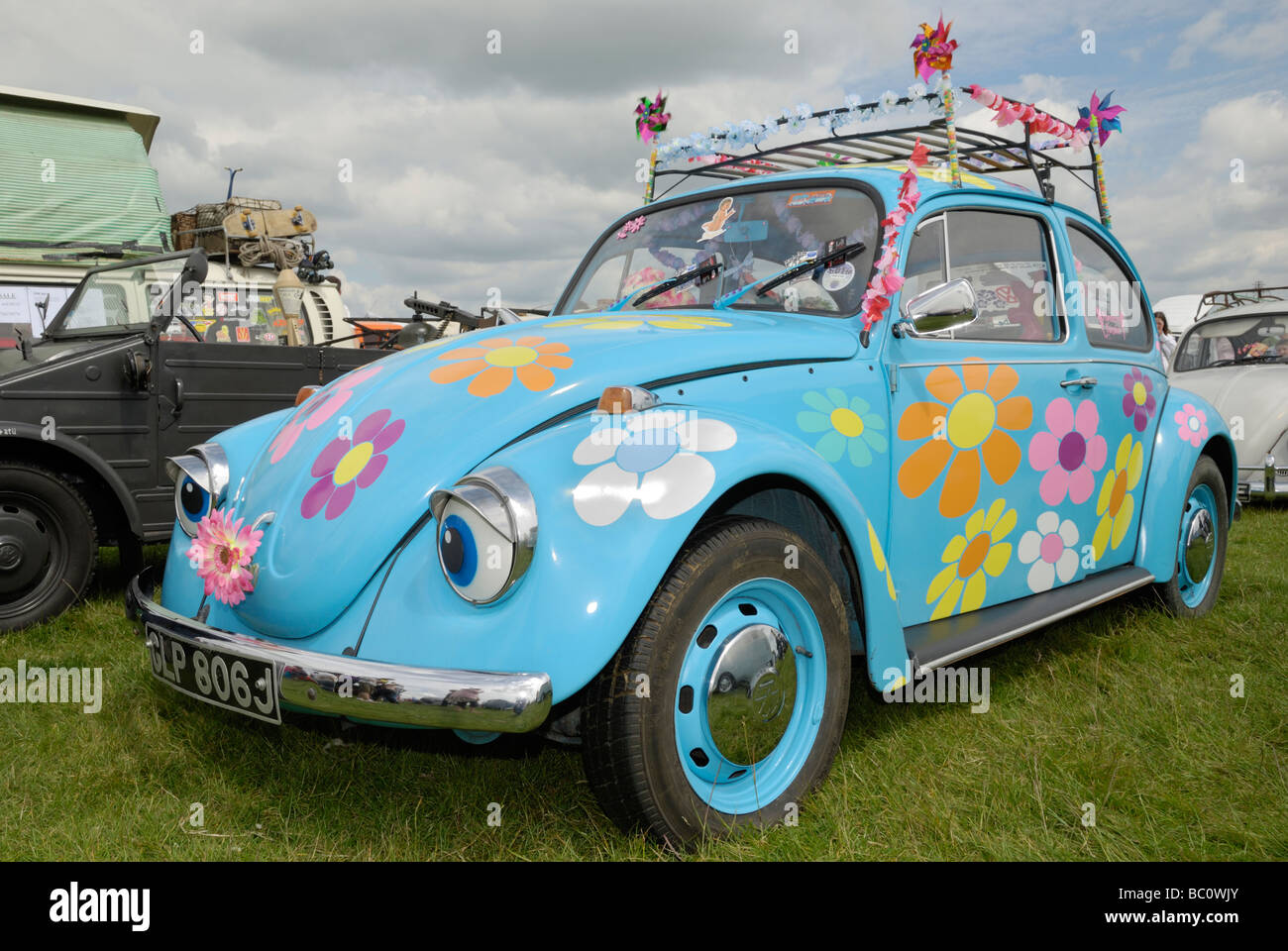 A VW Beetle decorated in a 'flower power' theme. Wymeswold, Leicestershire, England. - Stock Image