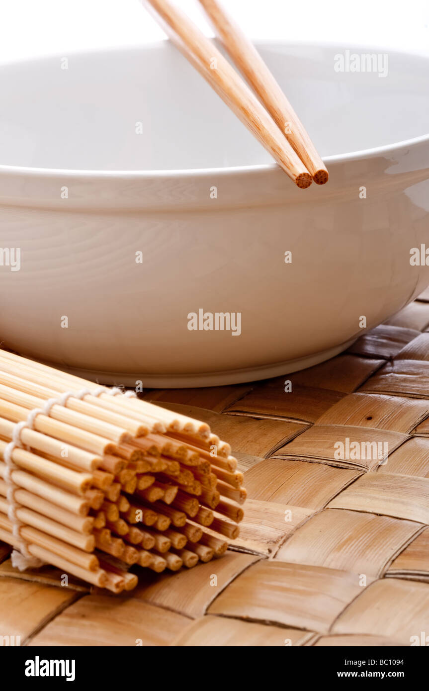 a vertical image of a pair of chopsticks on a white bowl with a suhi rolling mat on a weaved placemat - Stock Image