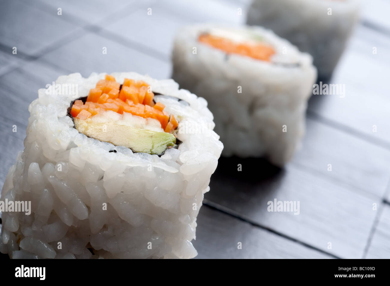 a tilted shallow focus horizontal macro of 3 rolls of sushi - Stock Image