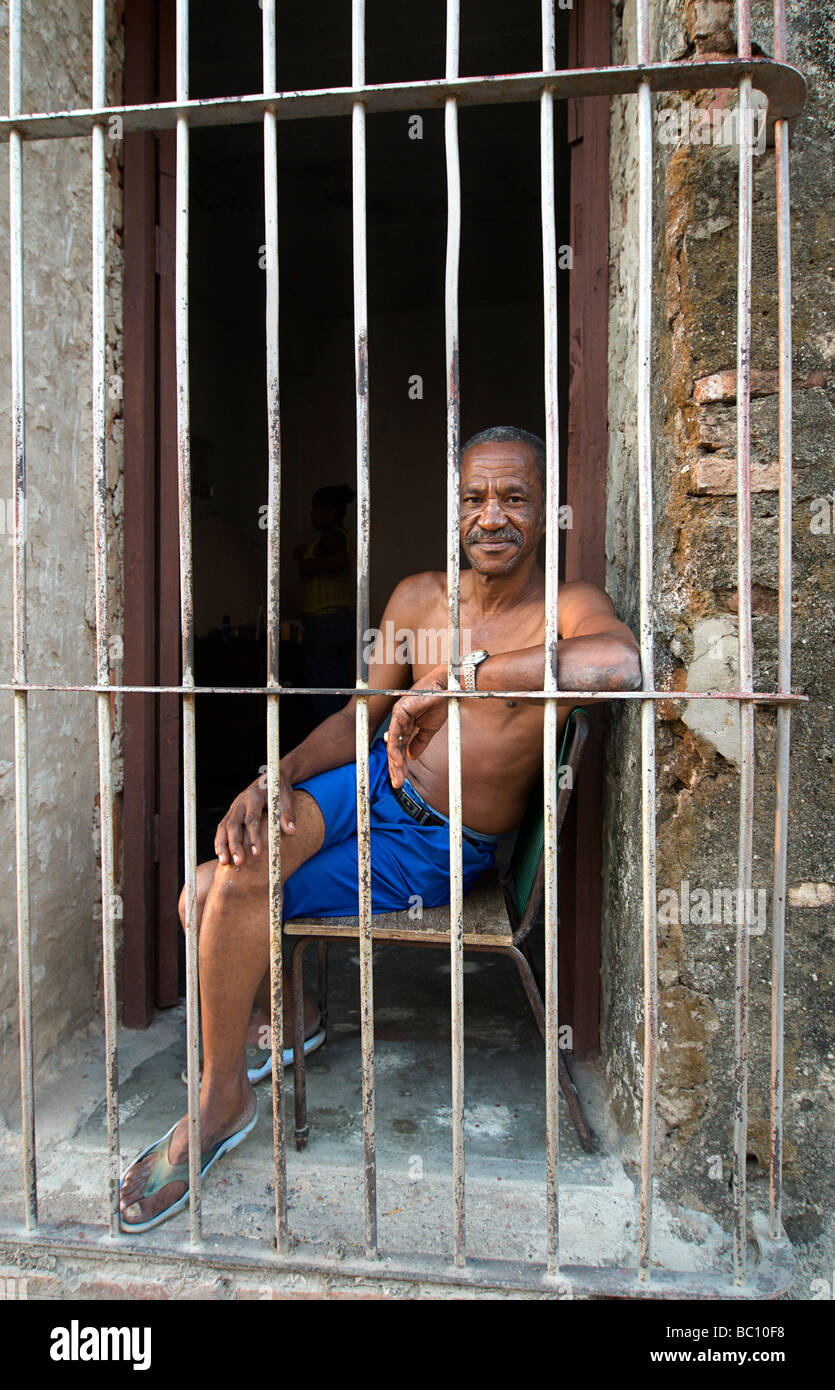 Friendly Cuban man sitting in the doorway of his Colonial home, Trinnidad, CUBA. MODEL RELEASED SUBJECT - Stock Image