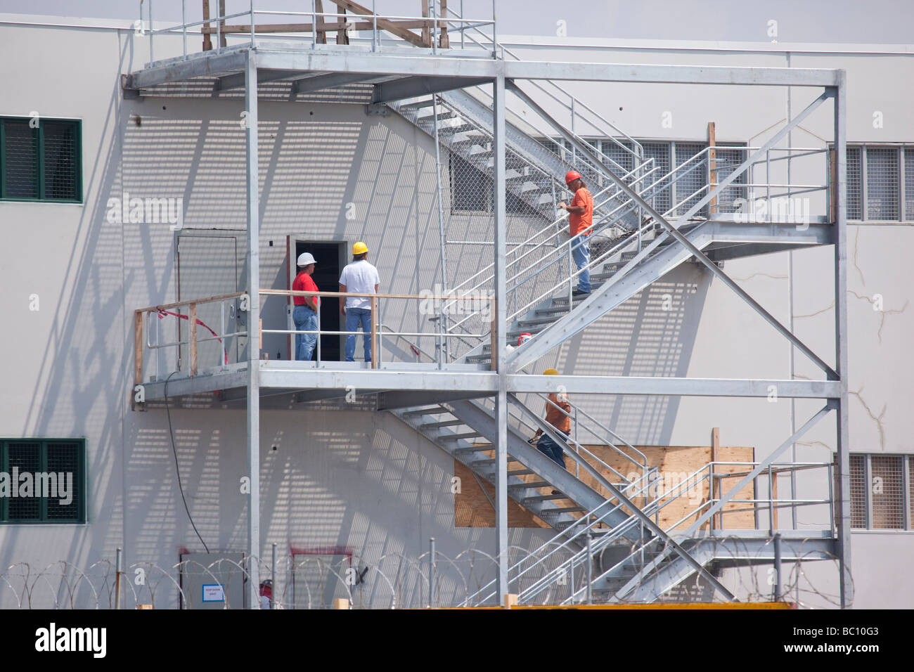 Construction workers in hardhats at a construction site - Stock Image