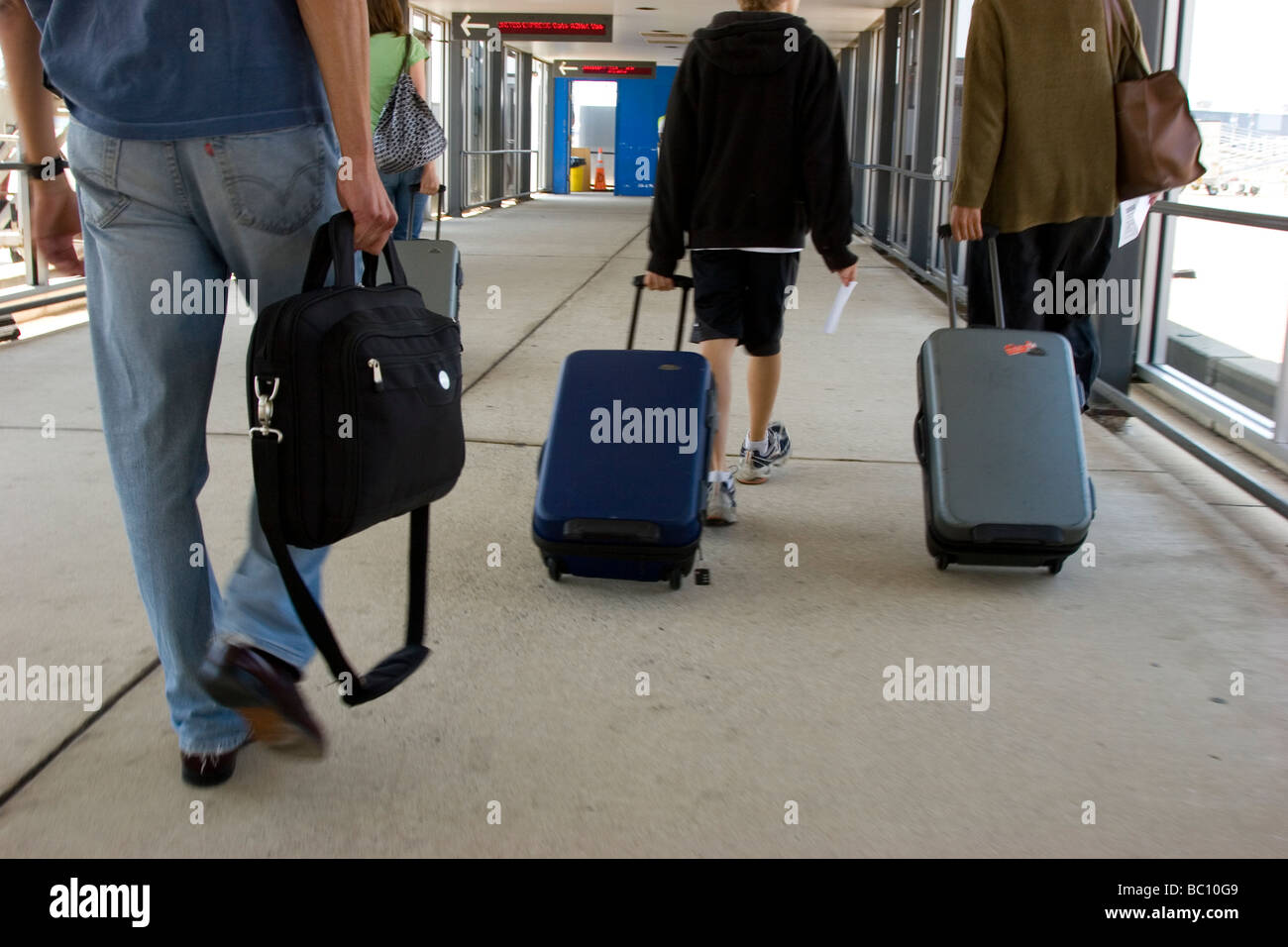 airline passengers walking with carry on luggage to airplane stock