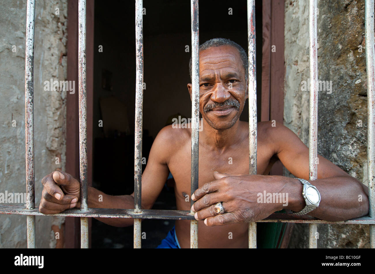 Friendly Cuban man sitting in the doorway of his  home, Trinnidad, CUBA. MODEL RELEASED SUBJECT - Stock Image