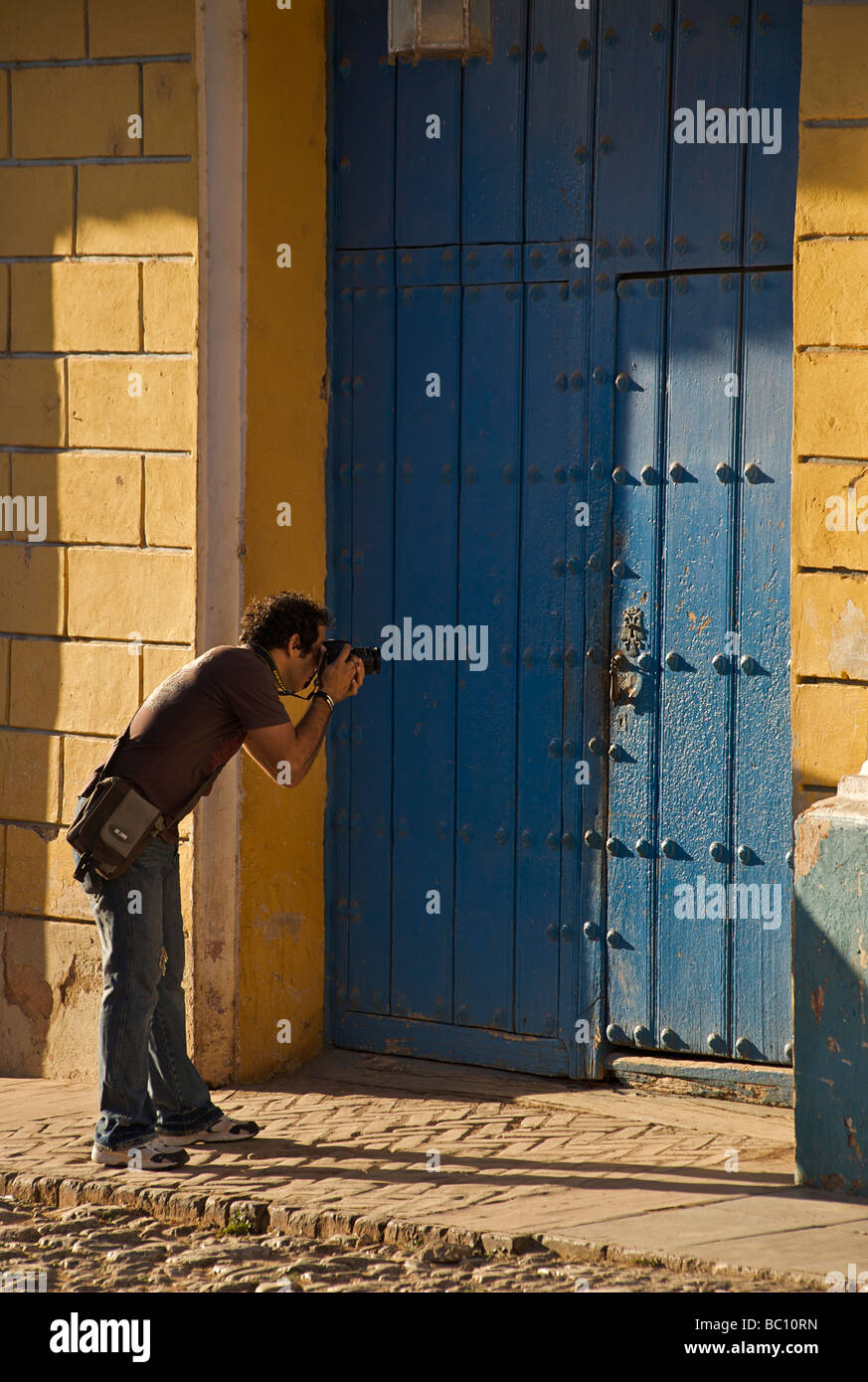 Photographer framing a detail of a Colonial door.  Trinidad, is a UNESCO World Heritage site. Stock Photo