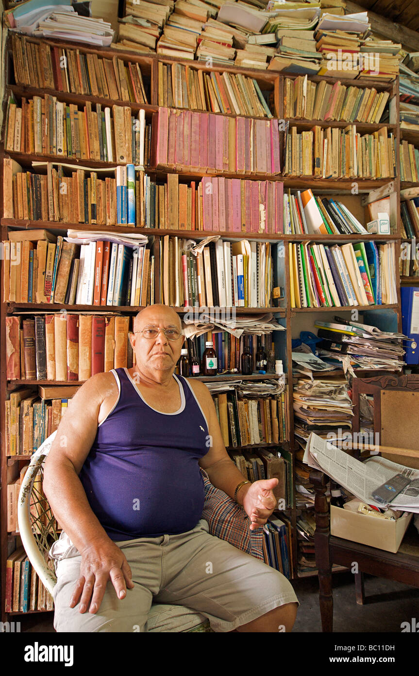 Welcoming and educated Cuban man with his personal library. Trinidad, Cuba. Model Released subject - Stock Image