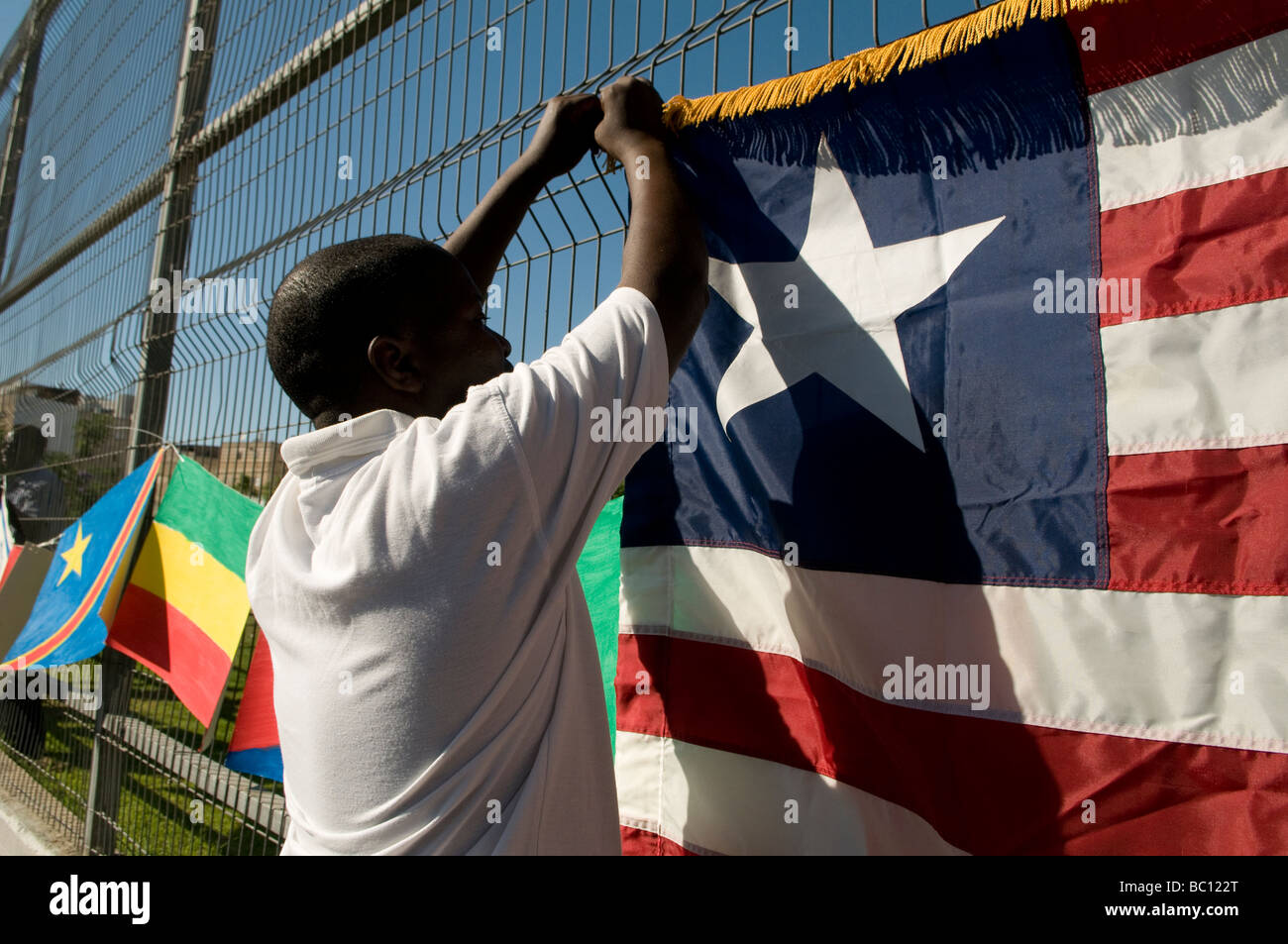 African migrant hanging African flags during UNHCR Refugee day event in Tel Aviv Israel - Stock Image