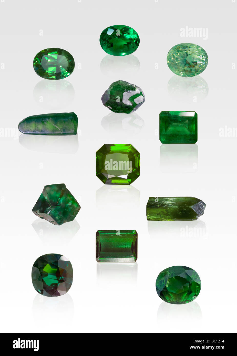 Green gemstone and crystal specimens on white background - Stock Image