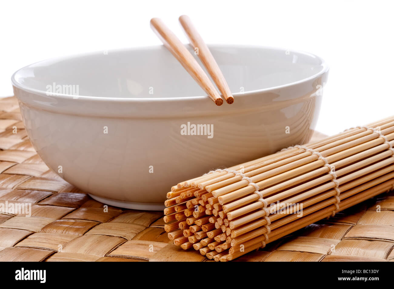 a horizontal image of a pair of chopsticks on a white bowl with a suhi rolling mat on a weaved placemat - Stock Image
