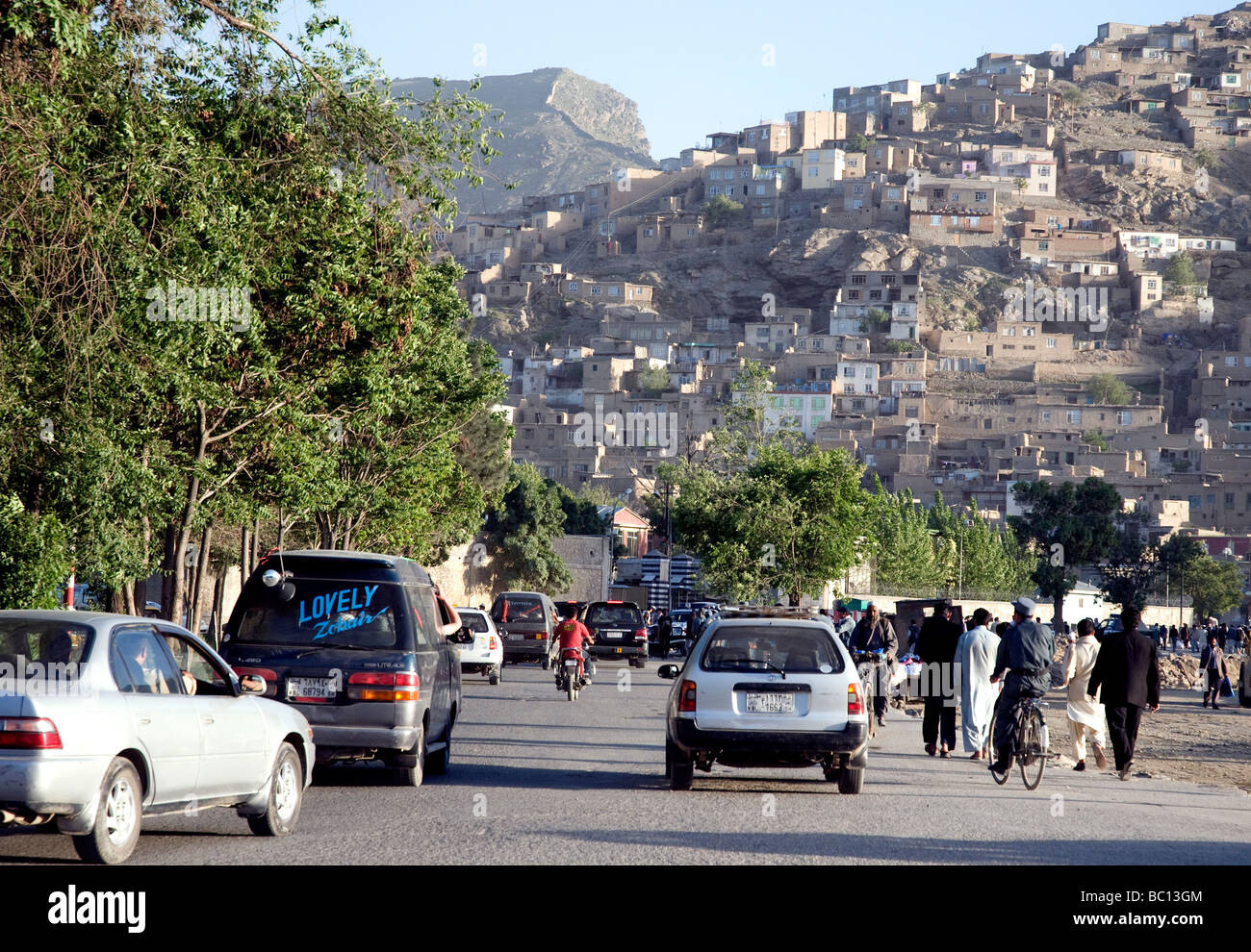 Traffic heading out of central Kabul towards a densely populated hillside; city population has hugely expanded in - Stock Image