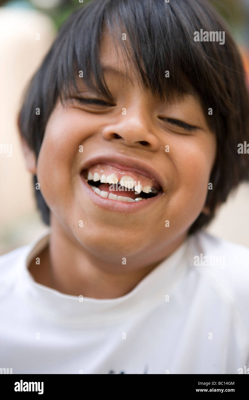 seven year old boy laughing at a friend's joke, closeup - Stock Image
