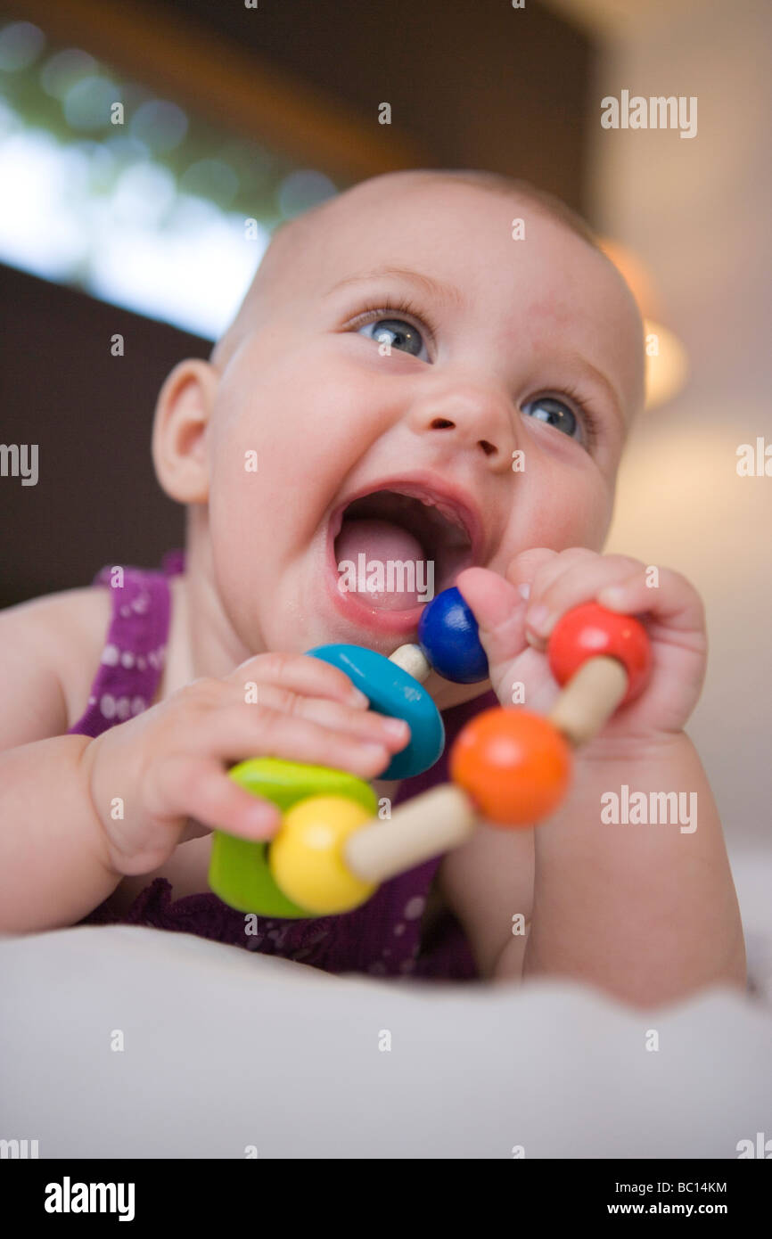 baby girl smiling and holding a wooden teething toy with mouth wide open - Stock Image