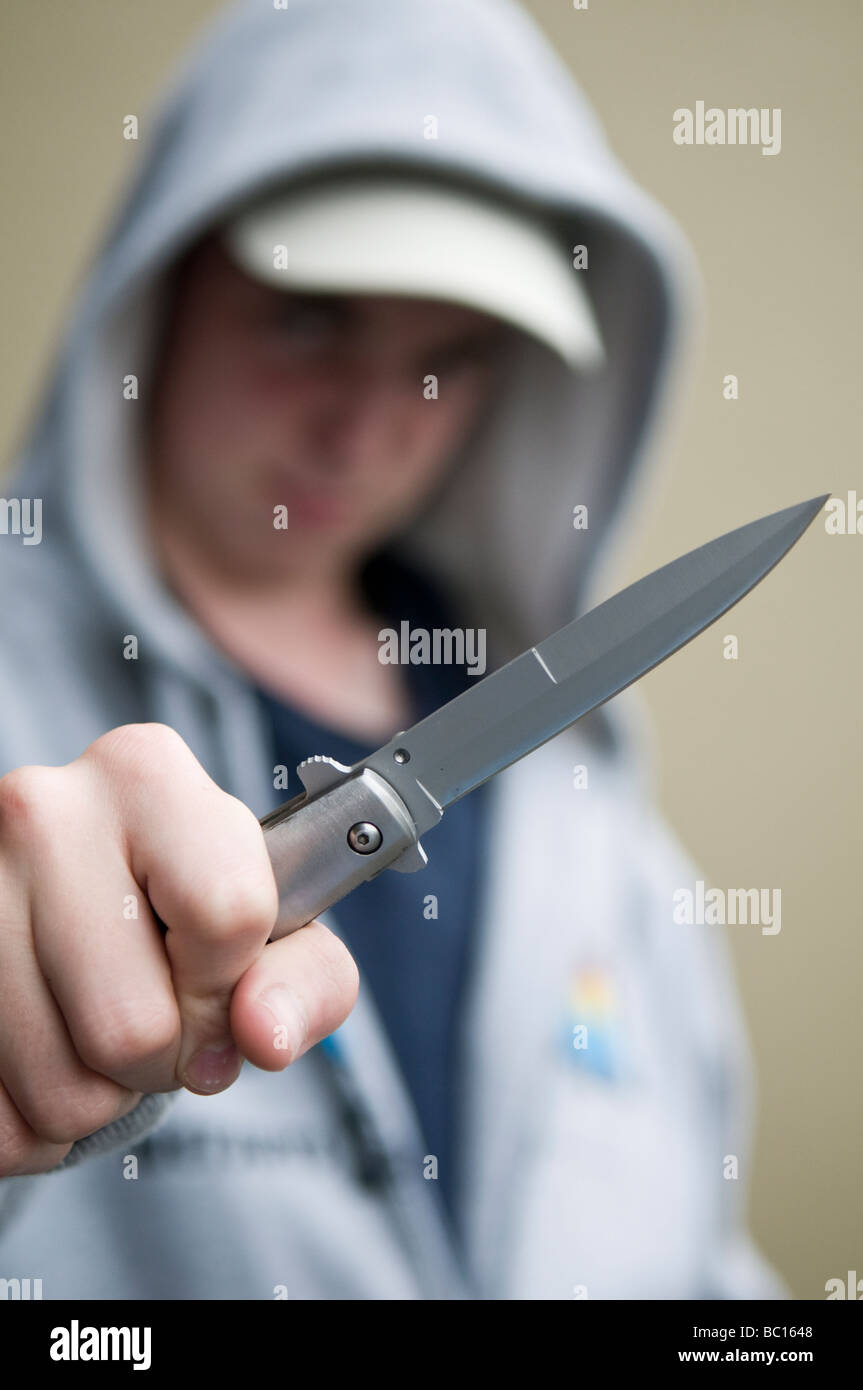 Youth in hoody brandishing flick knife - Stock Image