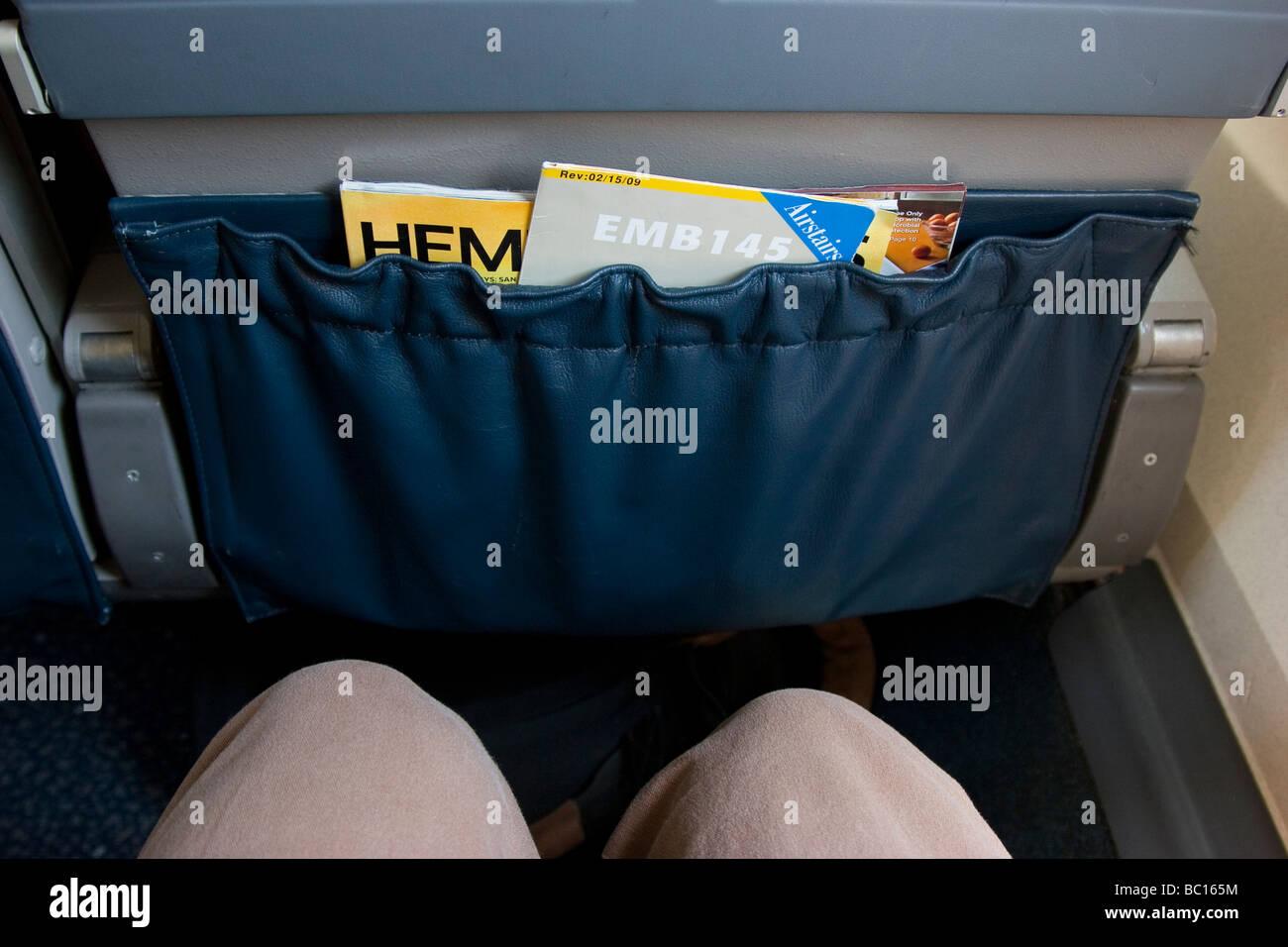 Lack of leg-room in airplane economy seat - Stock Image