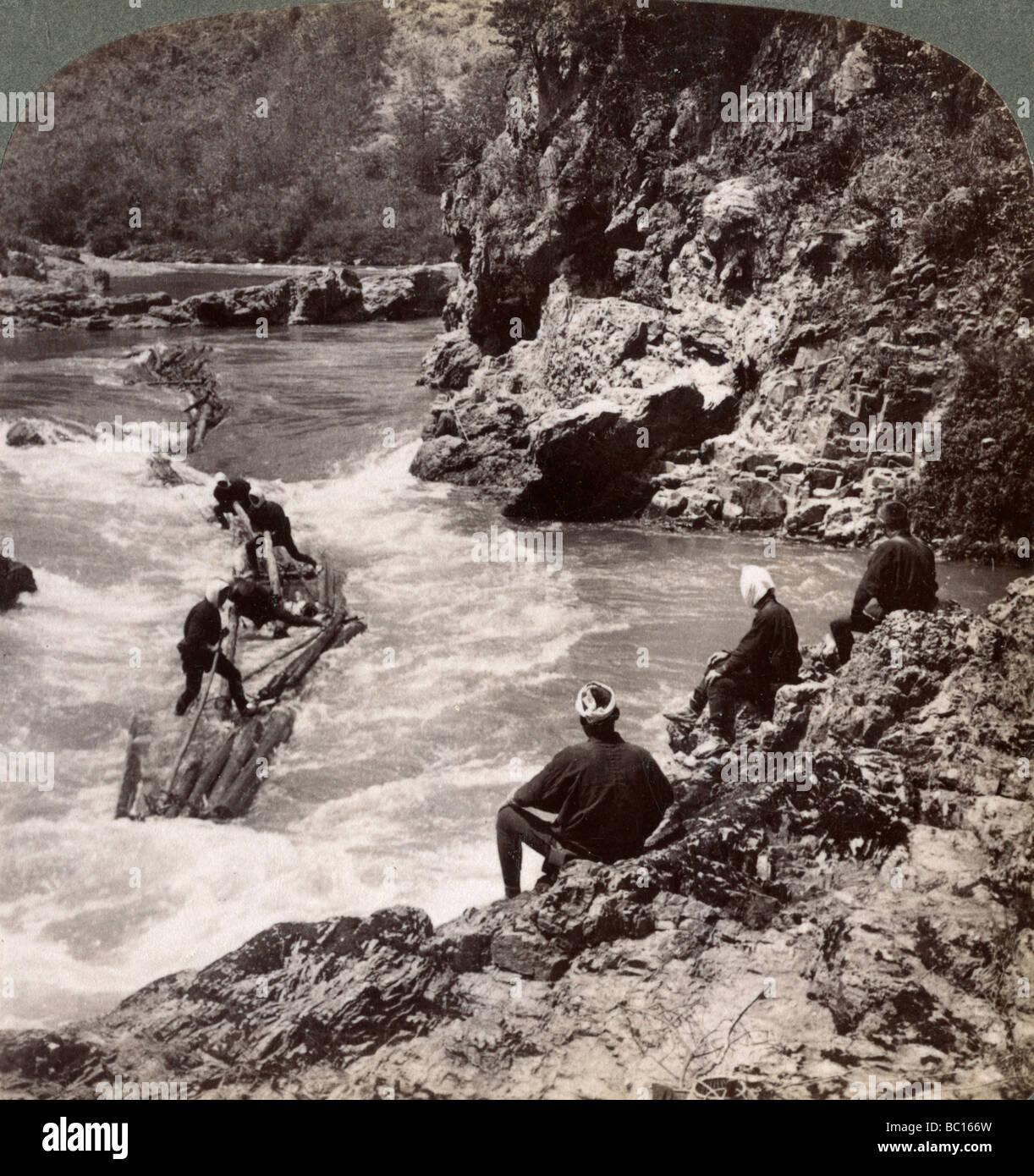 Men on a log raft, shooting the Hozu Rapids on the Katsura River, Kyoto, Japan, 1904. Artist: Underwood & Underwood - Stock Image