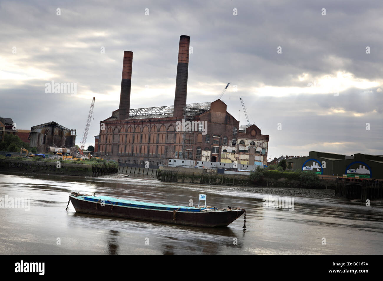 Shot of the River Thames with abandoned factory and resting boat. - Stock Image