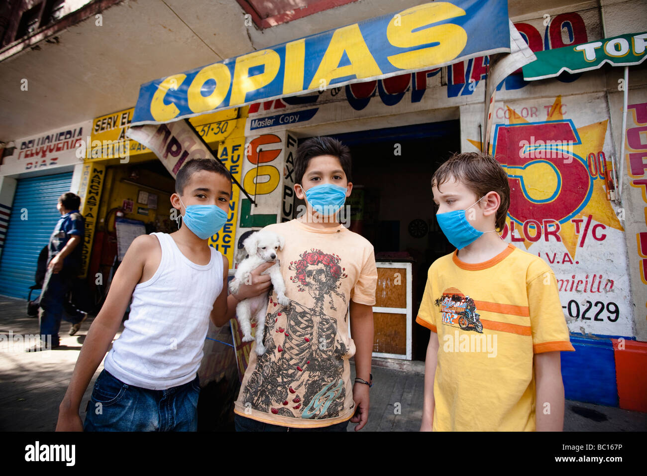 Three kids wearing masks holding a small puppy in the street during the swine flu epidemic in Mexico city, DF, Mexico. - Stock Image