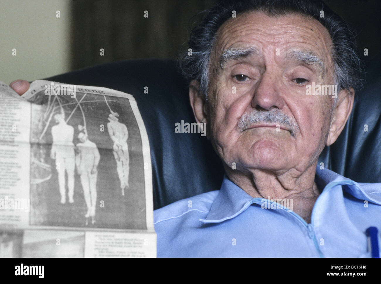 A senior man displaying a newspaper clipping depicting the last public lynching in Sonoma County, California. - Stock Image