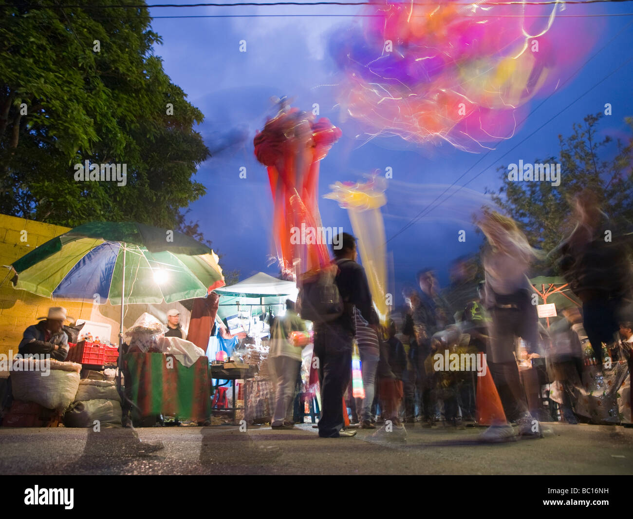 During a street festival, a man sells balloons at twilight. - Stock Image