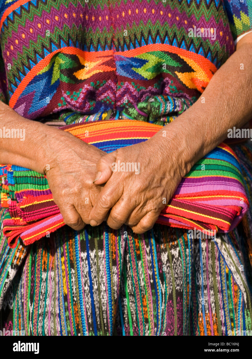 The hands of an indigenous Guatemalan woman holding traditional fabric. - Stock Image