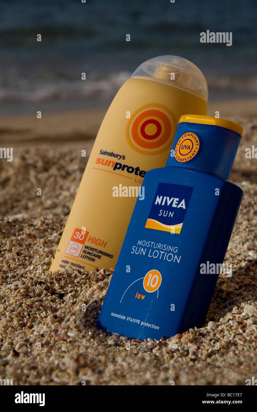 Bottles of suncream on an exotic beach - Stock Image