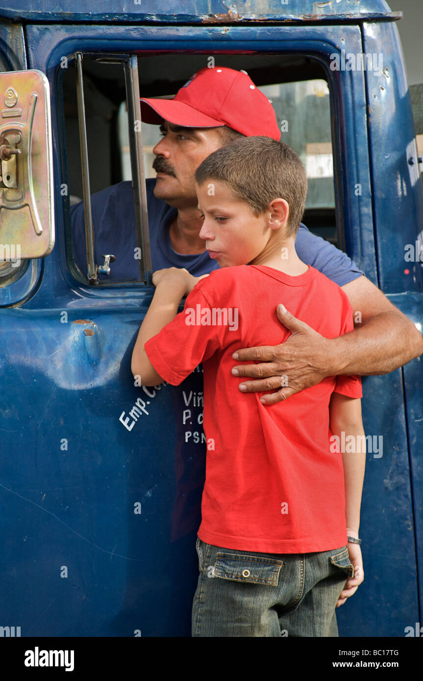 Cuban truck driver embracing his son at the window to his cab. Viñales, Pinar del Rio, CubaStock Photo