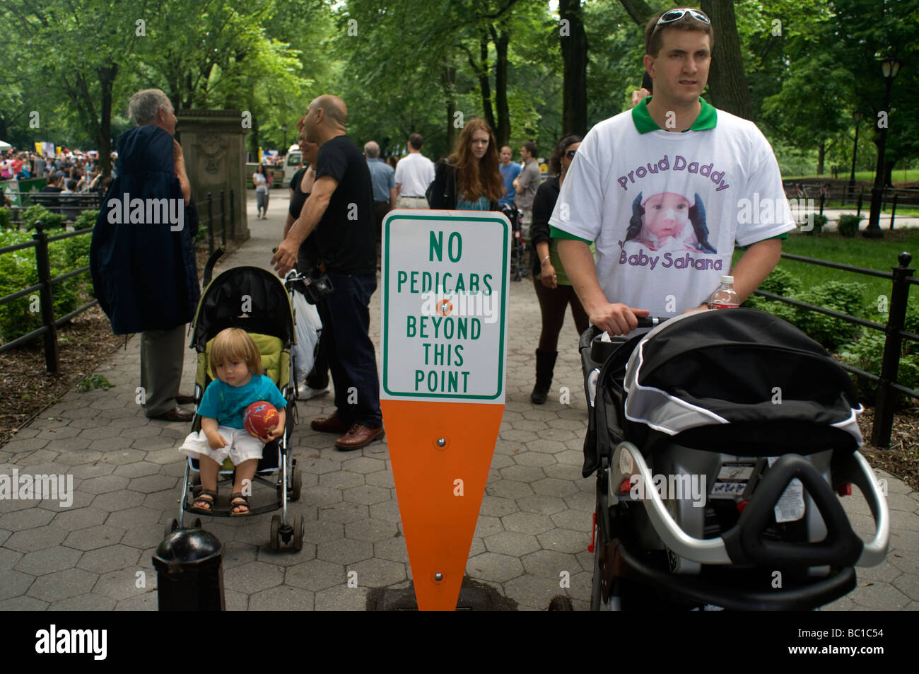 People and strollers pass a sign that prohibits pedicabs beyond this point in Central Park in New York - Stock Image