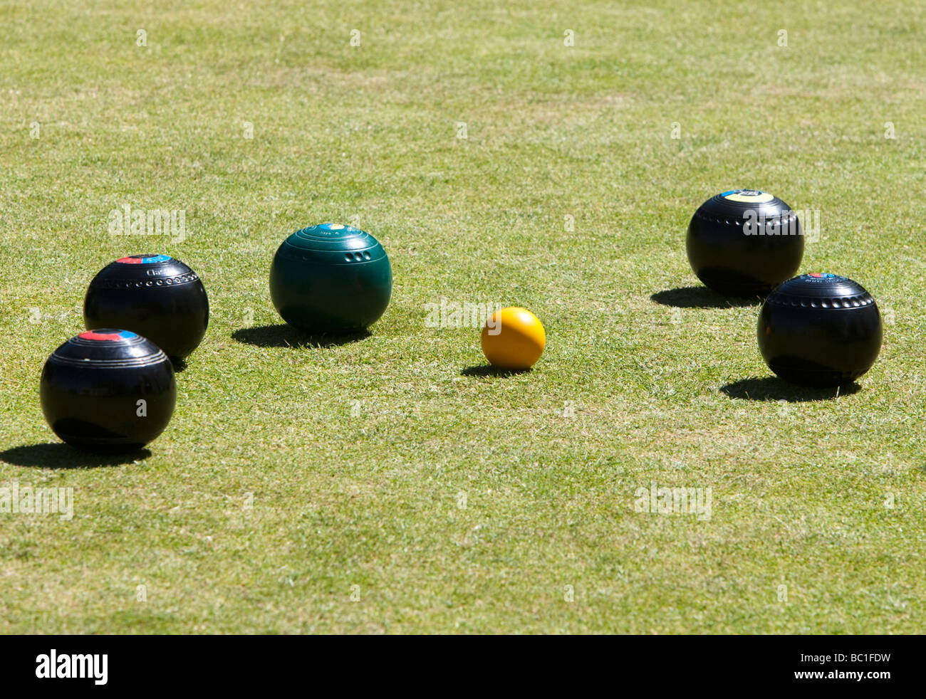 Woods surround the Jack during an afternoon game of bowls - Stock Image