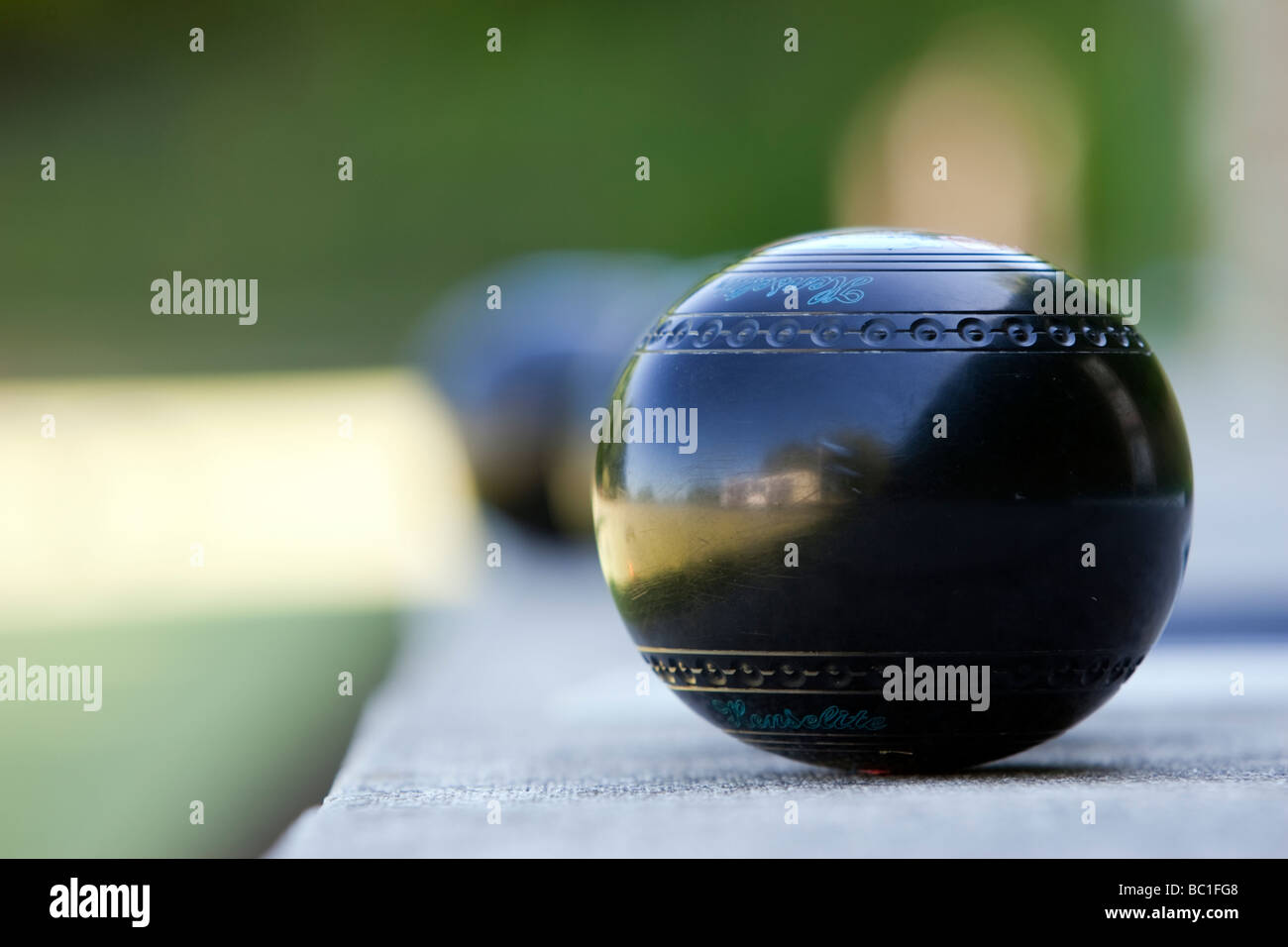 A wood sitting waiting to be played during a summer afternoon bowls match - Stock Image