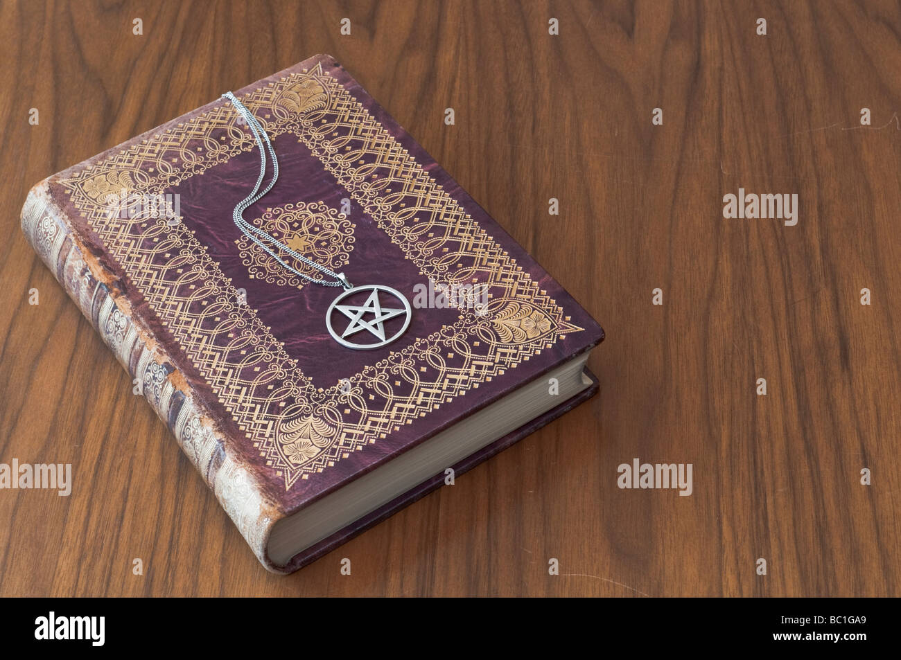 Silver necklace with inverted pentagram on an old book. - Stock Image