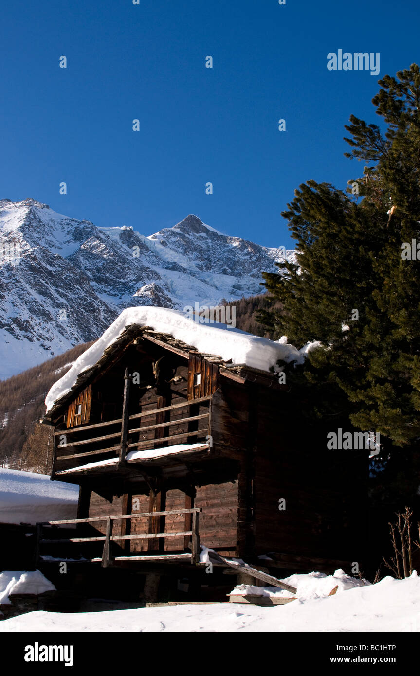 Snow capped traditional chalet in the Swiss Alps, Saas-Fe, Switzerland - Stock Image