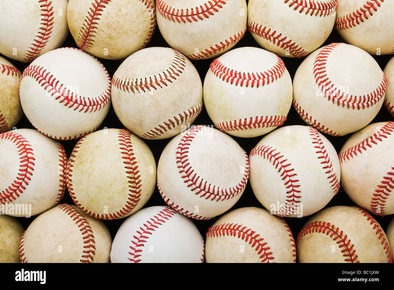 Downward view of group of used worn baseballs in tight rows, filling the whole image. - Stock Image