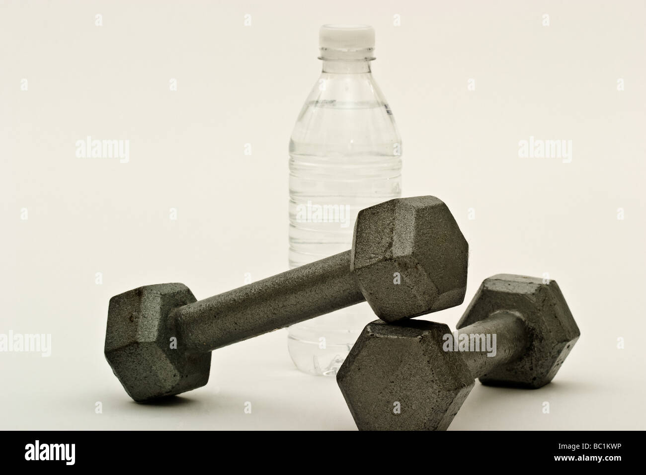 Two dumbbells in front of a bottle of water - Stock Image