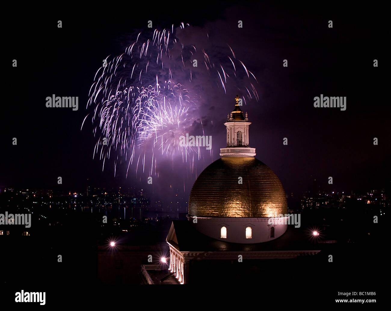 fourth of july fireworks explode in the sky over the charles river with the massachusetts state house in the foreground - Stock Image