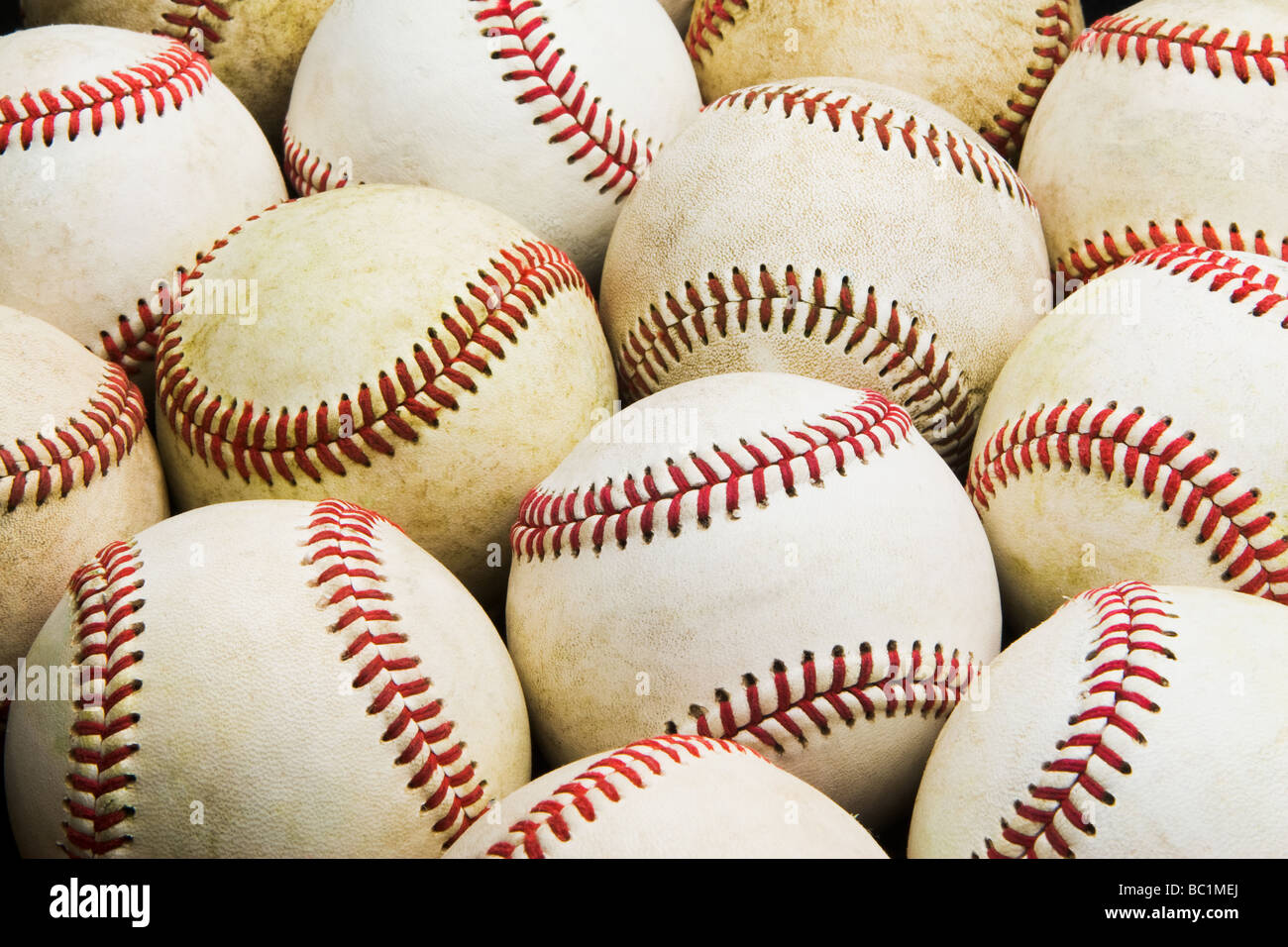 Downward, frontal view of group of used worn baseballs in tight rows fill the whole image - Stock Image