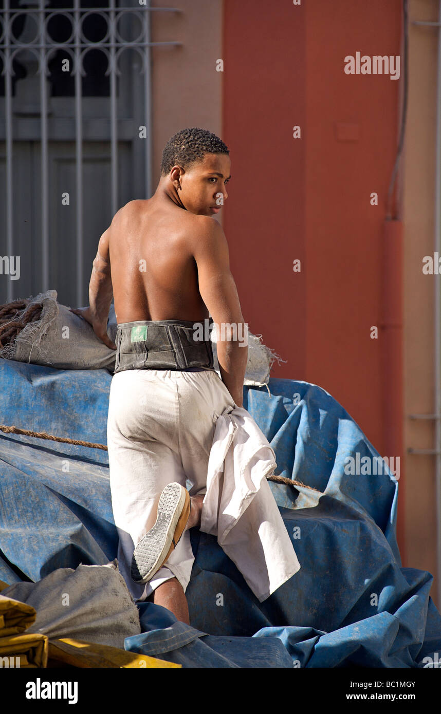 Cuban haulage worker on the back of a truck in Old Havana. Cuba Stock Photo