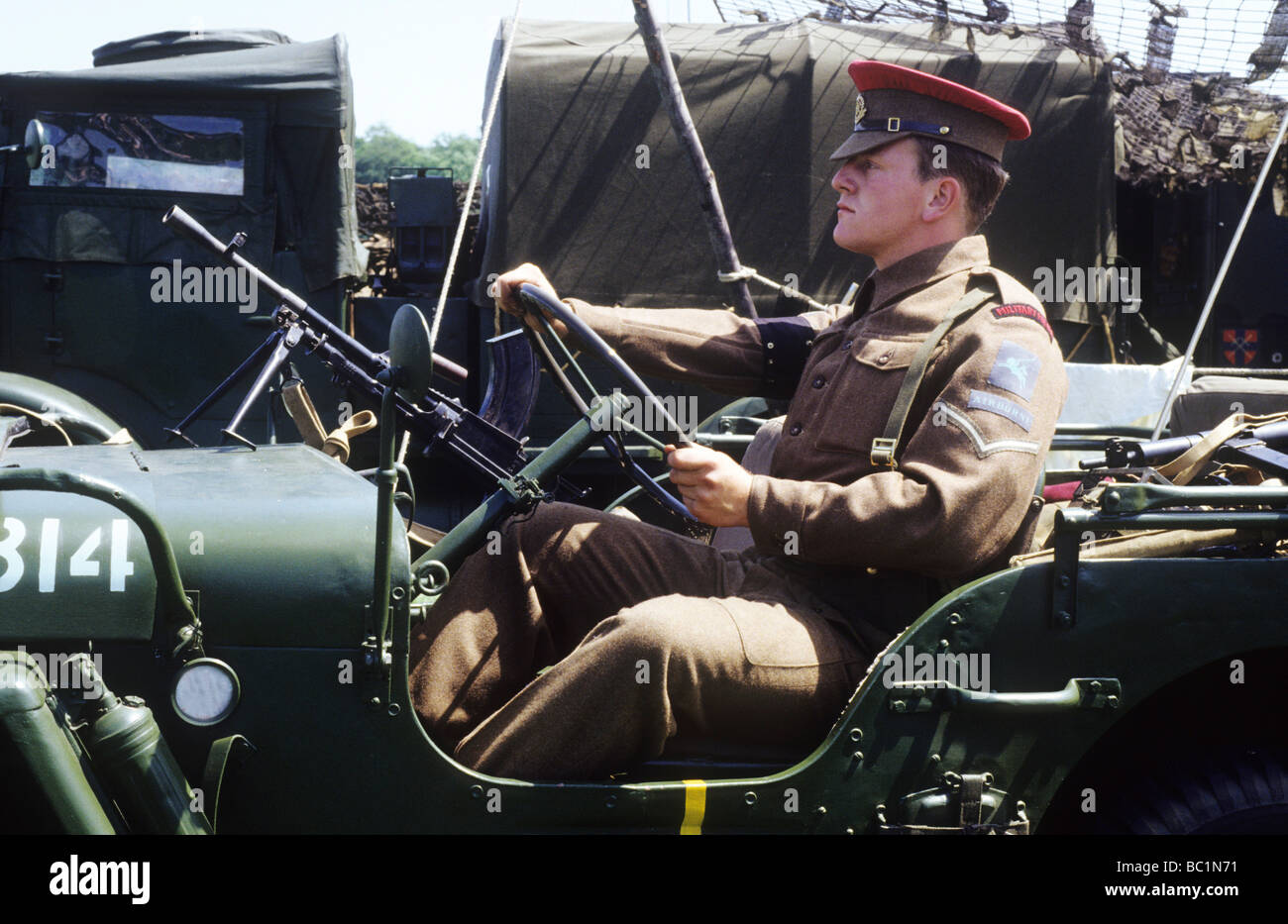 2nd World War historical re-enactment MP Military Policeman driving jeep redcap soldier uniform British Army khaki - Stock Image